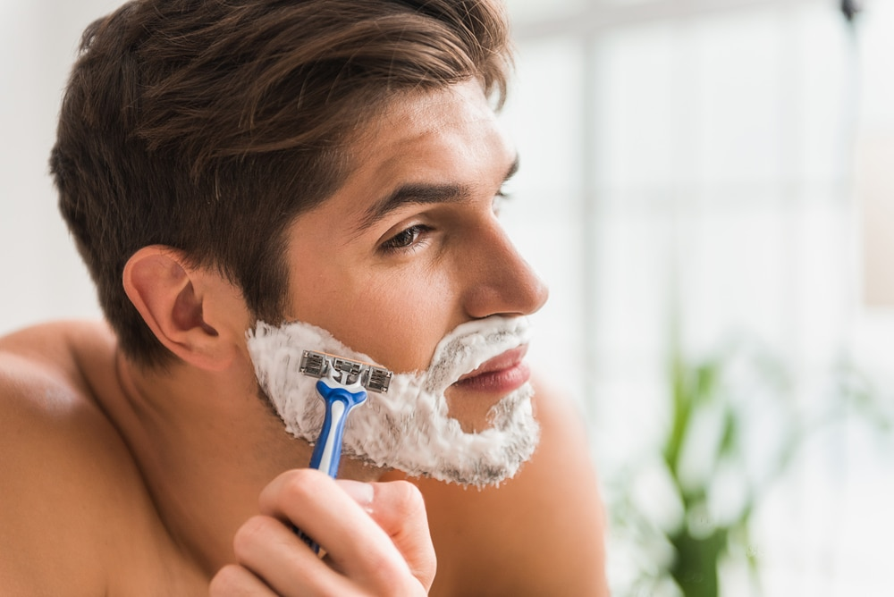 re serious guy shaving his beard